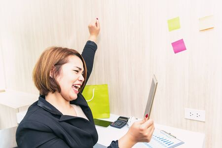 Business  technology concept .Happiness start up business woman raising arm in modern office working  having success. Start-up business team on meeting in modern bright office interior brainstorming