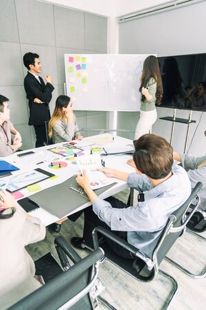 Teamwork business concept .Start up business people in modern office, working together having success. Multiethnic start-up business team on meeting in modern bright office interior brainstorming Stok Fotoğraf