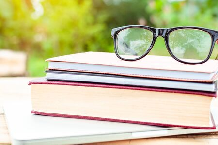 Vintage book and eye glasses for read and write over blurred nature outdoor background with copy space,selective focus ,education concept