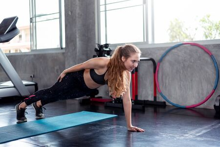 Young healthy caucasian woman practicing yoga stretch action pose on yoga mat in gym. Sporty girl happiness health care workout .Fitness,calmness and relaxing concept. Horizontal view. Stok Fotoğraf