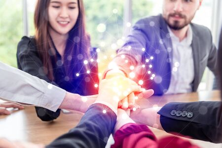 Multiracial business people collapse stacking hands over work table in modern meeting room.Teamwork join hands support together in office concept Banco de Imagens