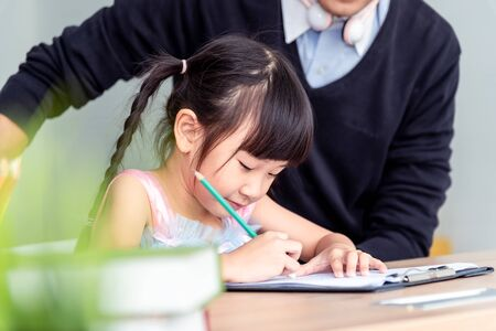 Happiness family leisure time in living room in holiday togetherness .Asian family having good time at home sitting on desk, playing drawing , little girl having fun. Education learning activity time. Banque d'images - 131857935