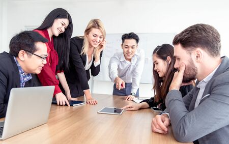 Teamwork business concept .Start up business people in modern office, working together having success. Multi ethnic start-up business team on meeting in modern bright office interior brainstorming . Banco de Imagens
