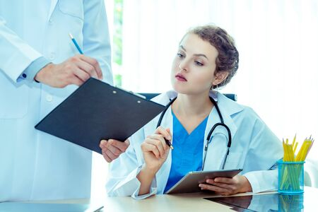 Experience male and female doctors orthopedics and team expert discussing x-ray film, surgery with the interpretation an x-ray in operating room in hospital .Medical technology and health care concept Фото со стока