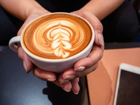 Hand woman holding a cup of hot latte arts coffee with cell phone and note on black table. Barista coffee art concept.with copy space Stockfoto