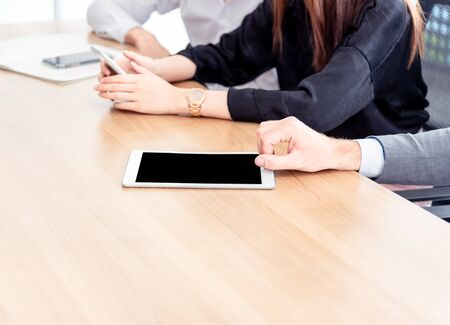 Closed up hands of business people with tablet pc with blank screen while sitting at the wooden table work in meeting room.Communicates brainstorming using a tablet computer technology concept. Banque d'images - 131857123