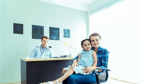 Young friendly caucasian pediatrician doctor is examining child patient girl with her mother ,consultation with a stethoscope and  tablet pc in clinic office .Healthcare and medical kid concept Reklamní fotografie