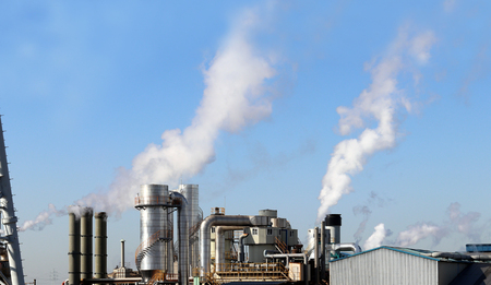 Thick plumes of smoke billowing from factory chimneys. Stock Photo