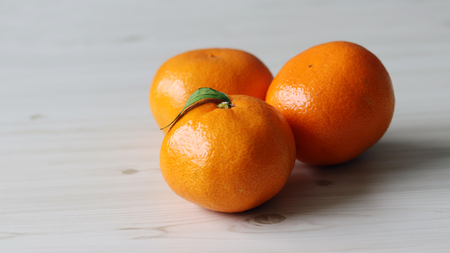 Three oranges on a wood background.