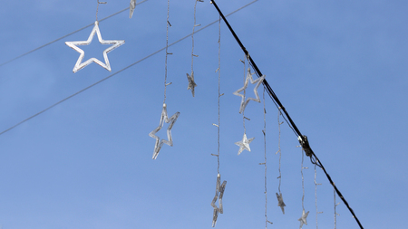 A model star clinging to a string against the sky