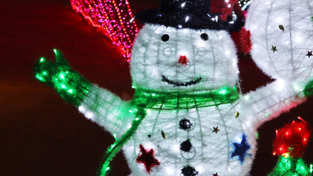 A white snowman tree lights up at night