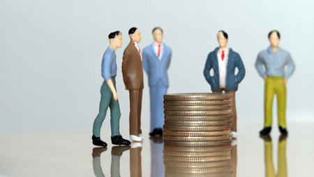 Money and human concept. Miniature people standing around a pile of coins