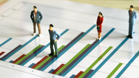 Gente en miniatura y el concepto gráfico. Miniatura de hombres y mujeres en un gráfico de barras.