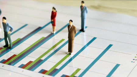 Miniature people and the graph concept. Miniature of people on a bar graph.