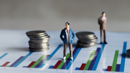 coins and miniature people. Performance and Wage Concepts. Stock Photo