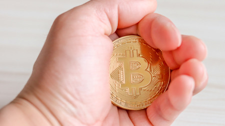 A hand holding a bitcoin tightly.