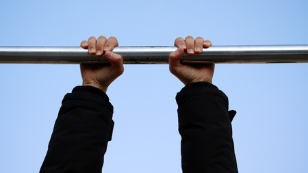 The need for light exercise during the winter. Hands hanging from an iron bar