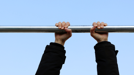The need for light exercise during the winter. Hands hanging from a pull-up bar