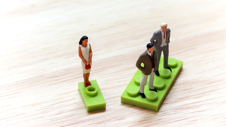 The concept of gender discrimination. Two miniature men and a miniature woman standing on a block of different size. Stock Photo