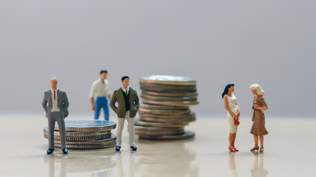 Men and women at work. Men standing in a pile of coins and women standing on the other side. Stock Photo