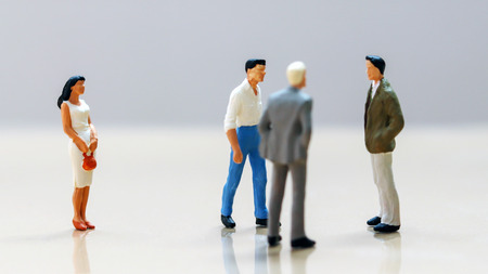 Men and women at work. Miniature woman standing on the other side of a group of miniature men. Stock Photo