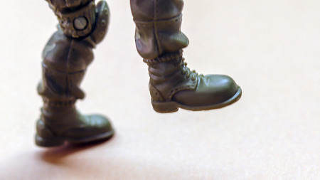 The leg and feet of a soldier figure.