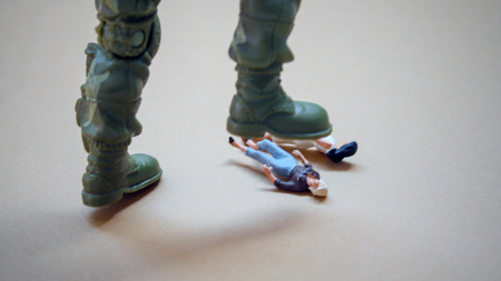 軍用ブーツの下のミニチュアの人々。