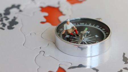 A miniature traveler sitting on a compass.