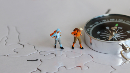 Two miniature tourists standing beside a compass.