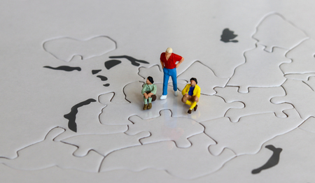 Miniature people on the world map puzzles. Stock Photo
