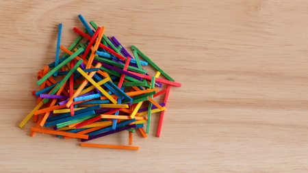 Multicolored wooden sticks on the wood background.