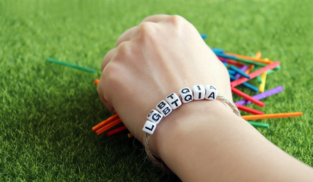 A bracelet hand of LGBTQIA cube and colorful wooden stick. Stock Photo