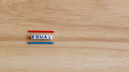 EQUAL text cube and two color sticks on the wood background. 스톡 콘텐츠