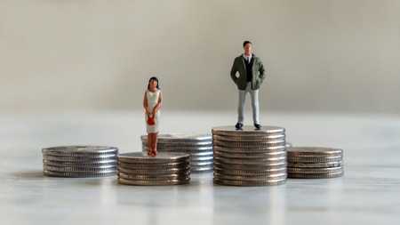 A miniaturization of a man and a woman on a coin tower. Stock Photo