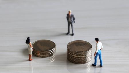 Bild von oben genommen. Miniaturmann und Miniaturfrau, die vor einem Stapel Münzen von verschiedenen Höhen stehen.