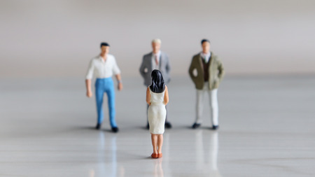 Three miniatures men and one miniature woman face each other. Stock Photo