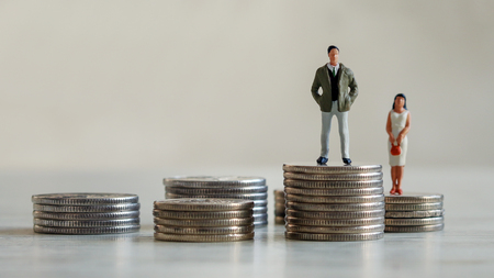 Gender discrimination concept. A miniature man and a miniature woman standing on the coin. Stock Photo