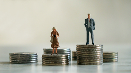 Concept of gender discrimination in pay. A miniature man and a miniature woman standing on top of a pile of coins. Stockfoto
