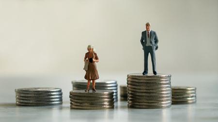 Concepto de discriminación de género en el pago. Un hombre en miniatura y una mujer en miniatura de pie sobre una pila de monedas.