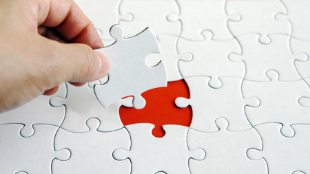 A hand holding a piece of the puzzle. A piece of a puzzle.
