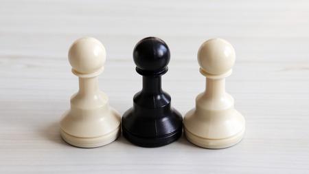 Two white chessmen and a black chessman.