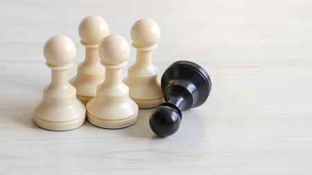 Four white chessmen and a black chessman. Stock Photo