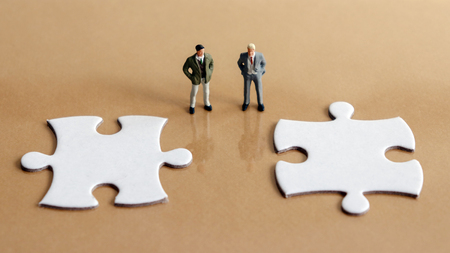Two miniature men and two puzzle pieces. Фото со стока