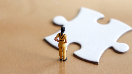 A miniature looking down at a piece of the puzzle.