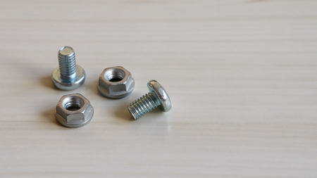 Two bolts and two nuts on the wood background. Because bolts and nuts are different shapes, they need each other. 版權商用圖片