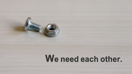 We need each other. Bolt and nut on the wood background. 스톡 콘텐츠