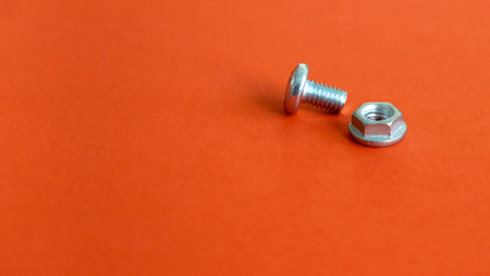 Bolt and nut on the red background.