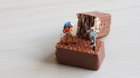 A miniature man and a miniature woman climbing a backpack on a chocolate. Stock Photo
