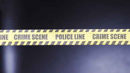 Police Line tape with black background Stock Photo