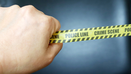 A hand holding a Police tape. Police Line tape with black background Stock Photo